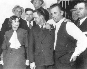Джон Диллинджер в тюрьме Краун-Пойнта, Индиана, доставлен после захвата в Туксоне, Аризона. Слева направо: Шериф Лилиан Холли, прокурор Роберт Эстил, Диллинджер и шеф.