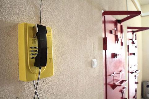 Внутри корпуса, где содержатся т.н. малолетние, висят телефоны. Отсюда, при отсутствии замечаний, можно позвонить родным. Металлический угол не позволяет открыть камеру настежь — в оставшееся пространство может выйти только один человек