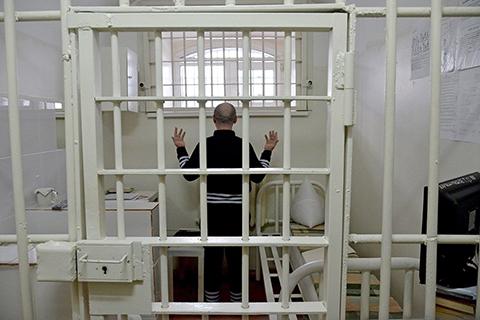 Можно подумать, он молится. Нет, это такая поза при открытии двери в камеру. Осужденный должен показать надзирателю пустые руки. Самых опасных, как этого вора в законе, содержат в одиночках