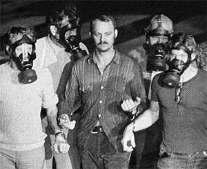Ян-Эрик Олссон под конвоем полицейских одетых в противогазы