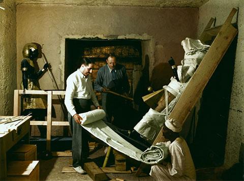 Говард Картер, Артур Каллендер и египетский рабочий заворачивают одну из часовых статуй для транспортировки
