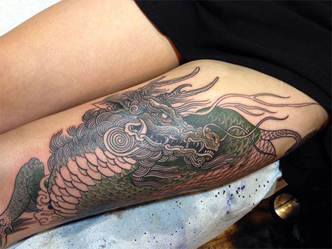 Татуировка дракона на женском бедре