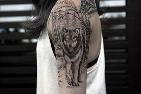 Тату волк в лесу - на руке у девушки