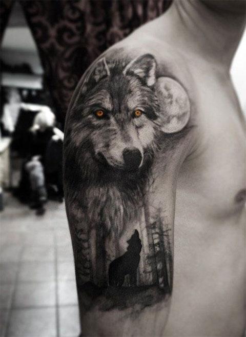 Тату волк в лесу - на руке у мужчины