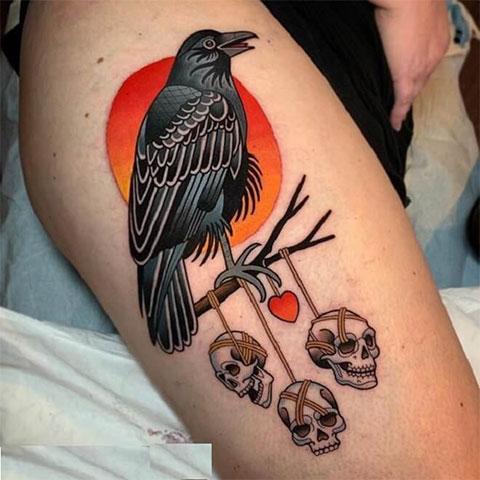 Цветная татуировка с вороном на бедре у девушки