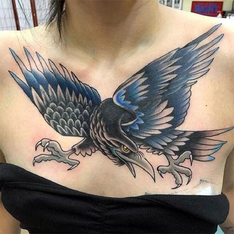 Татуировка ворон на груди девушки - фото