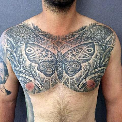 Необычное тату на груди с папоротником и бабочкой