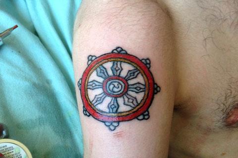 Тату колесо Сансары на руке