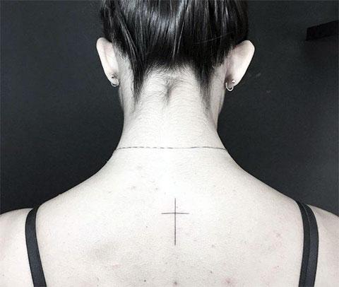 Маленький крест на спине у девушки - фото татуировки