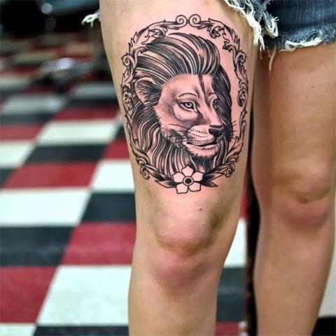 Татуировка лев на бедре девушки - фото