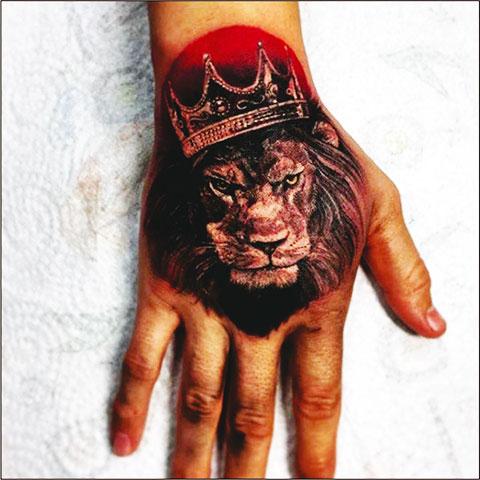 Тату лев с короной на запястье