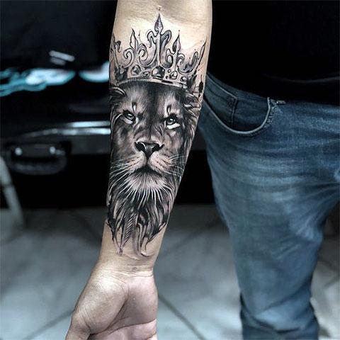 Тату лев с короной у мужчины на руке