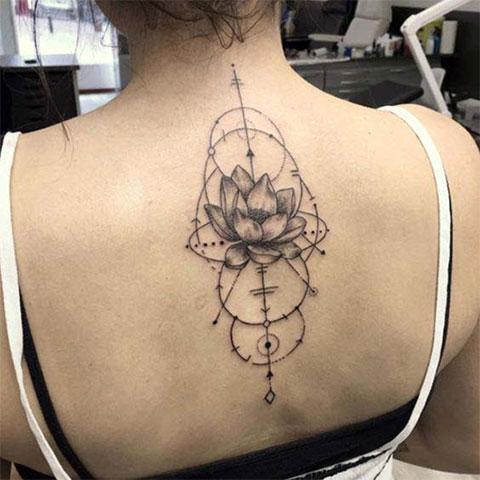 Женская татуировка с цветком лотоса на спине