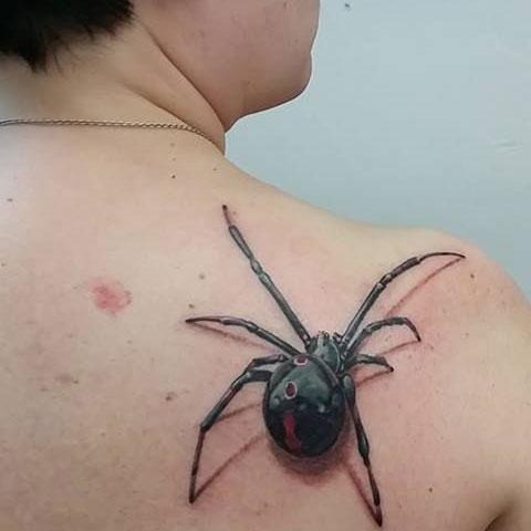 Паук на спине - женская татуировка