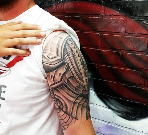 Татуировка в стиле биомеханики на плече
