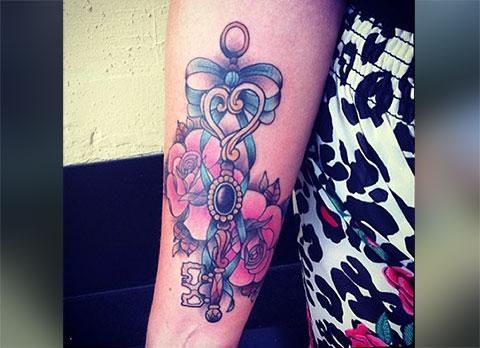 Цветная тату с цветами на руке у девушки