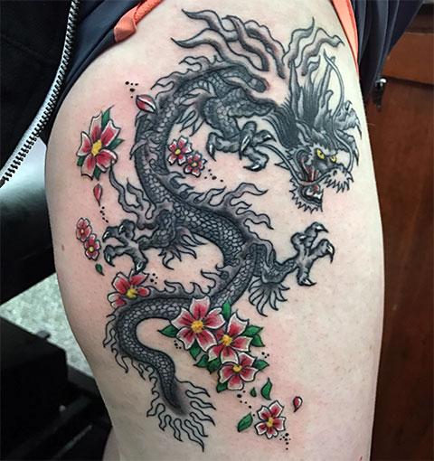 Тату китайский дракон у девушки на бедре