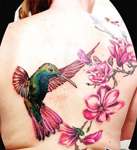 Цветная тату колибри с цветком на спине у девушки - фото