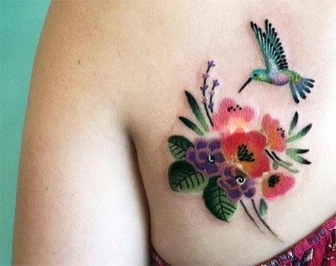 Цветная тату колибри с цветком на лопатке у девушки - фото