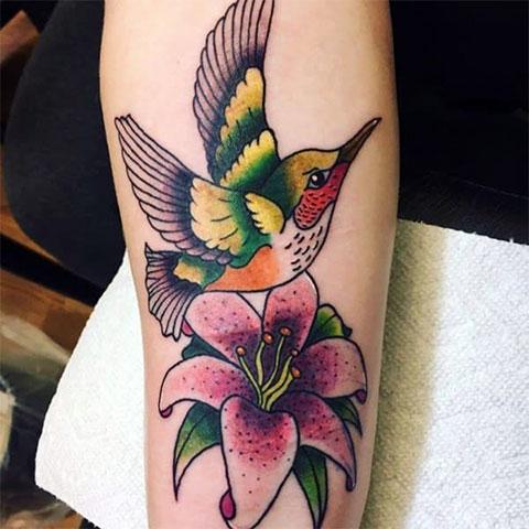 Цветная тату колибри с цветком на руке у девушки - фото