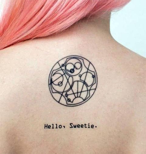 Тату символы с надписью на спине у девушки