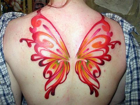 Цветная татуировка крылья на спине у девушки - фото