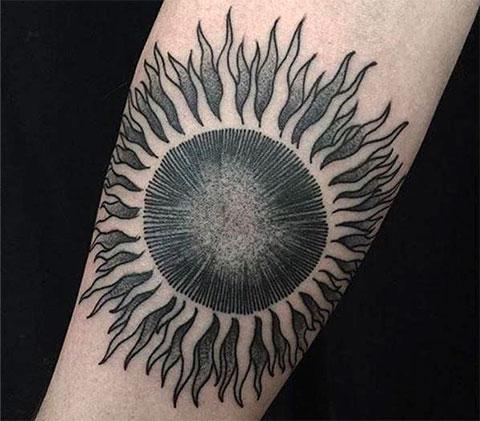 Татуировка черное солнце на руке