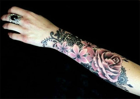 Татуировка с цветами и розой у девушки на предплечье