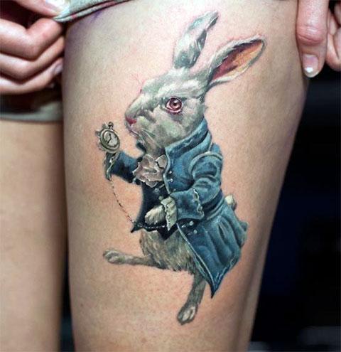 Тату с кроликом из Алисы в стране чудес на ноге у девушки