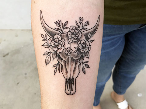 Татуировка телец и цветы на руке у девушки