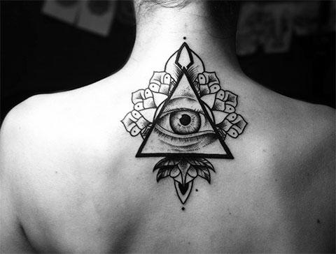 Тату глаз в треугольнике на спине у девушки - фото