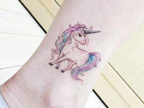 Татуировка с маленьким единорогом на щиколотке у девушки