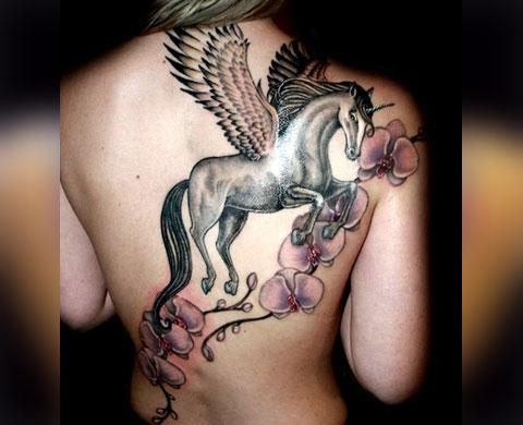 Татуировка у девушки - единорог с крыльями и цветами на спине