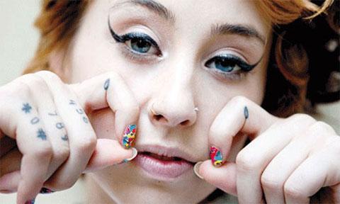 Татуировка слезы на пальцах у девушки