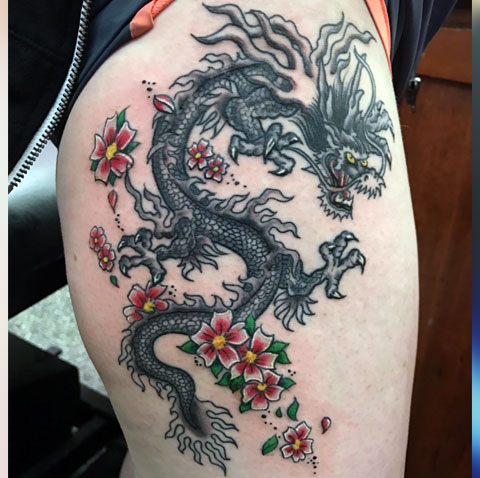 Тату дракон с цветами на бедре