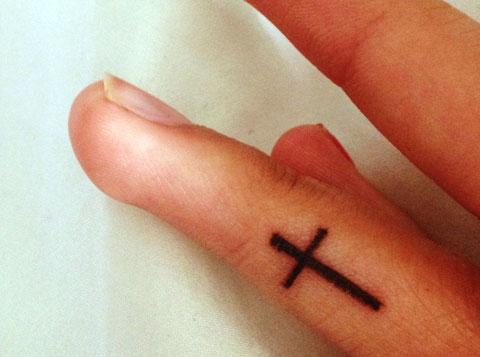 Тату крест между пальцев