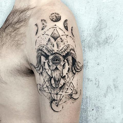 Татуировка в стиле дотворк у мужчины на плече