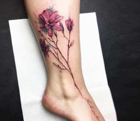 Татуировка магнолия на женской ноге