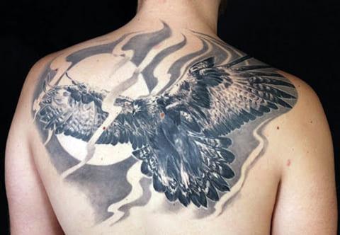 Татуировка с парящим орлом на спине у мужчины - фото