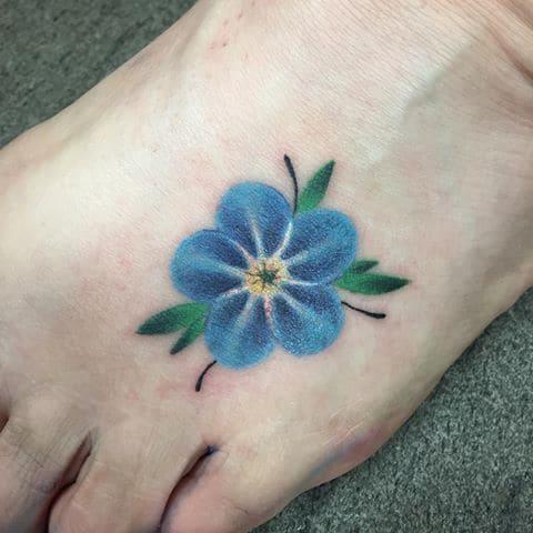 Татуировка с незабудкой на ноге