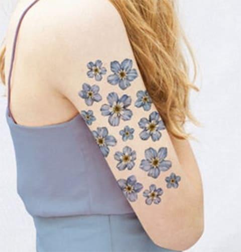 Тату цветков незабудки на руке девушки