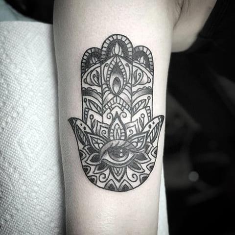 Татуировка у девушки на руке - рука Фатимы с глазом