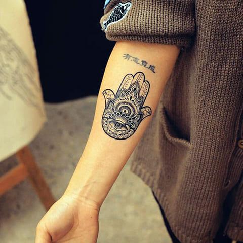 Хамса - татуировка на руке у девушки