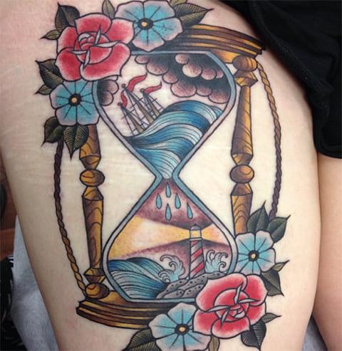Тату песочные часы с цветами на бедре у девушки