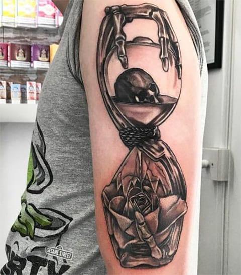Тату песочных часов с черепом внутри на руке