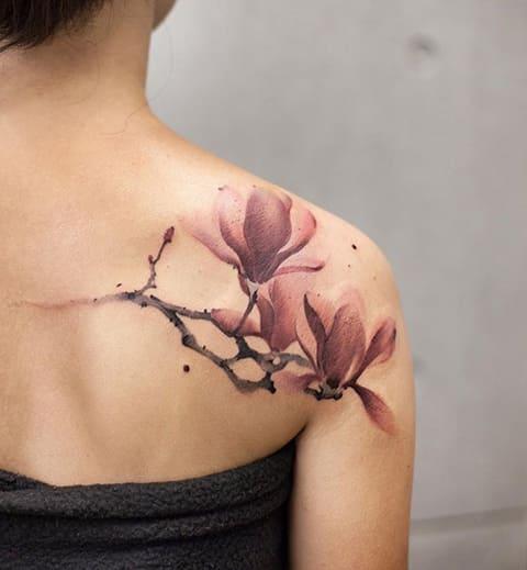 Татуировка магнолии на лопатке у девушки