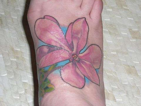 Татуировка магнолии на ступне у девушки