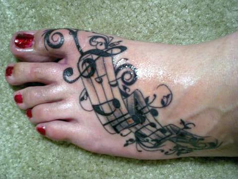 Татуировка с нотами на ступне у девушки