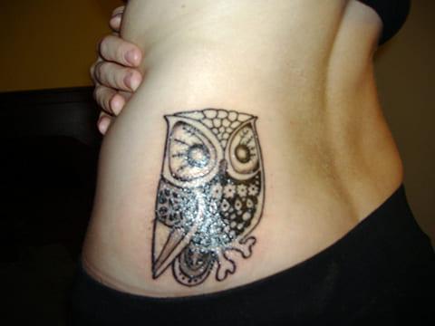 Женская татуировка с совой на боку
