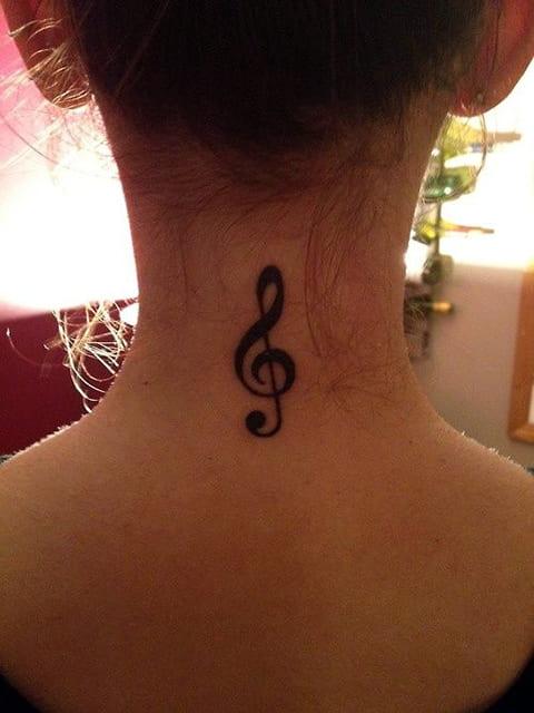 Скрипичный ключ татуировка на затылке у девушки